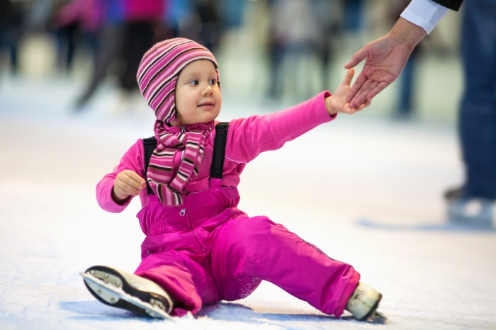 Pretty little girl skates sitting on the ice at the rink