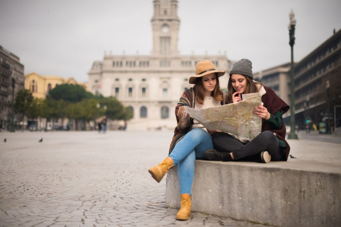 Female friends consulting a city map in the winter