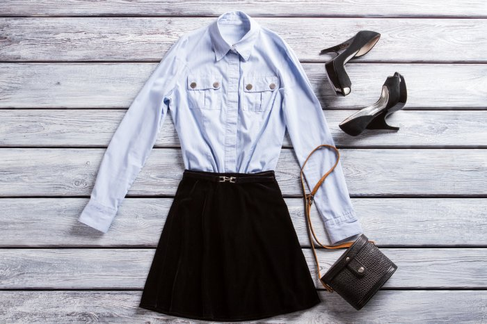 Light blue shirt and heels. Heel shoes and black skirt. Casual evening outfit with purse. Woman's classic bag with strap.