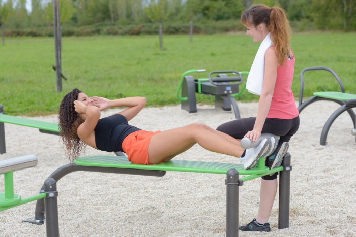 Lady holding feet of friend doing situps