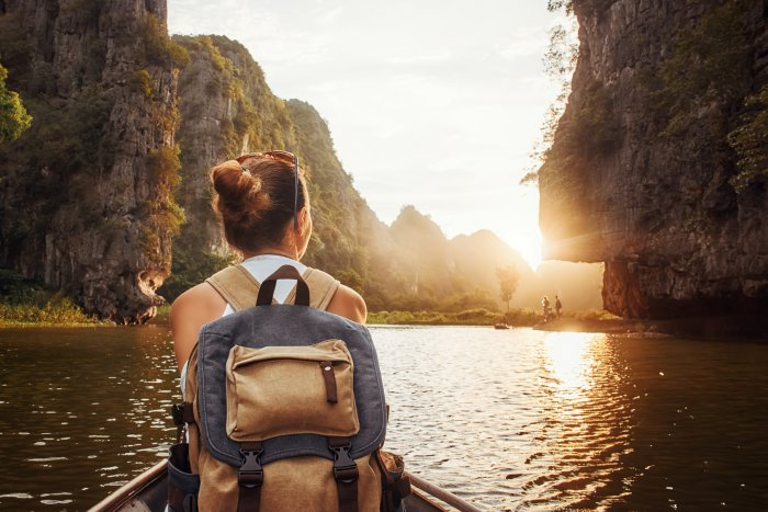 Woman with backpack swims on boat among karst mountains to meet her friends. Tam Coc, North of Vietnam. Travel and active lifestyle, summer holiday concept.