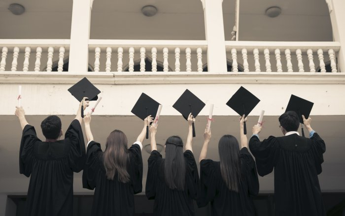 Group of graduate students holding their diploma