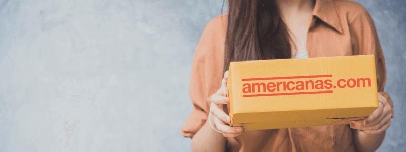 Mulher segurando uma caixa de papelão com o logo da Americanas.com