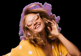 Mulher com um óculos e com a mão no pescoço sorrindo. Ela veste uma camisa amarela com alguns circulos brancos.